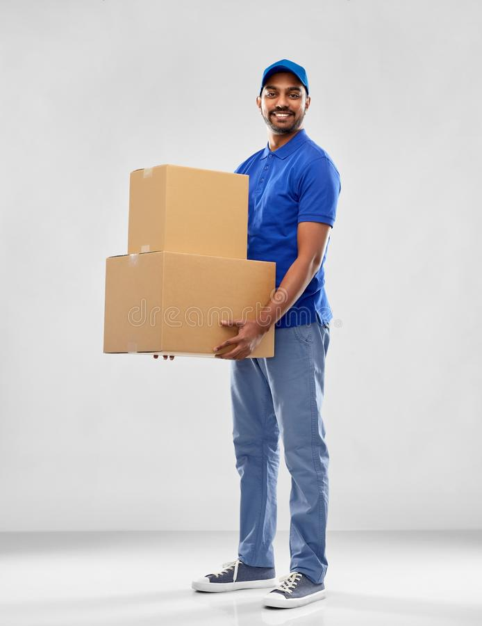 Happy indian delivery man with parcel boxes. Mail service and shipment concept - happy indian delivery man with parcel boxes in blue uniform over grey background stock photo