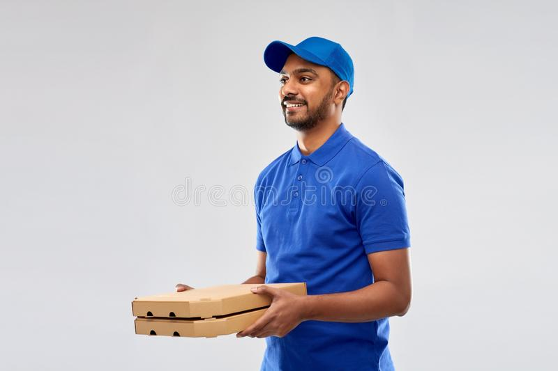 Happy indian delivery man with pizza boxes in blue. Service and people concept - happy indian delivery man with pizza boxes in blue uniform over grey background royalty free stock image