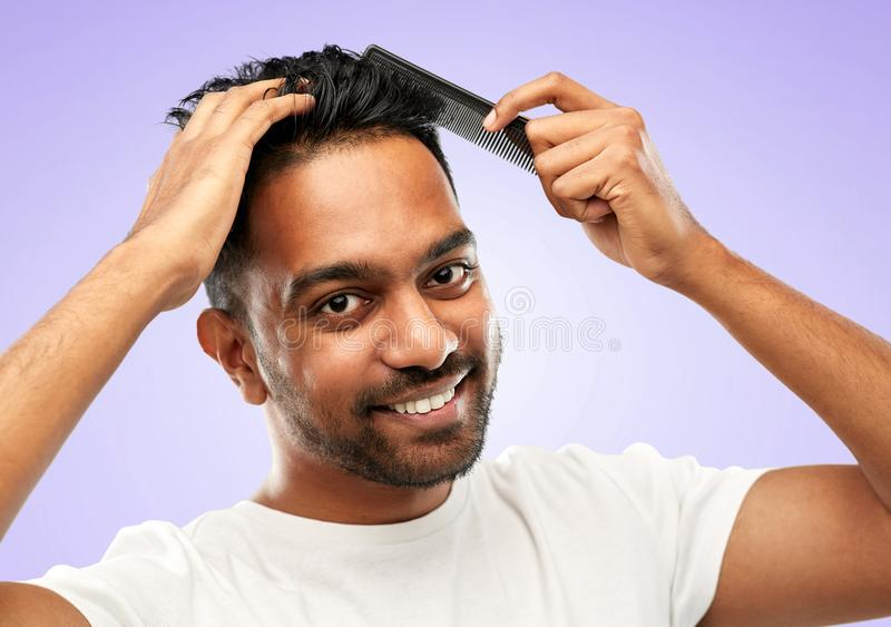 Happy indian man brushing hair with comb royalty free stock photo