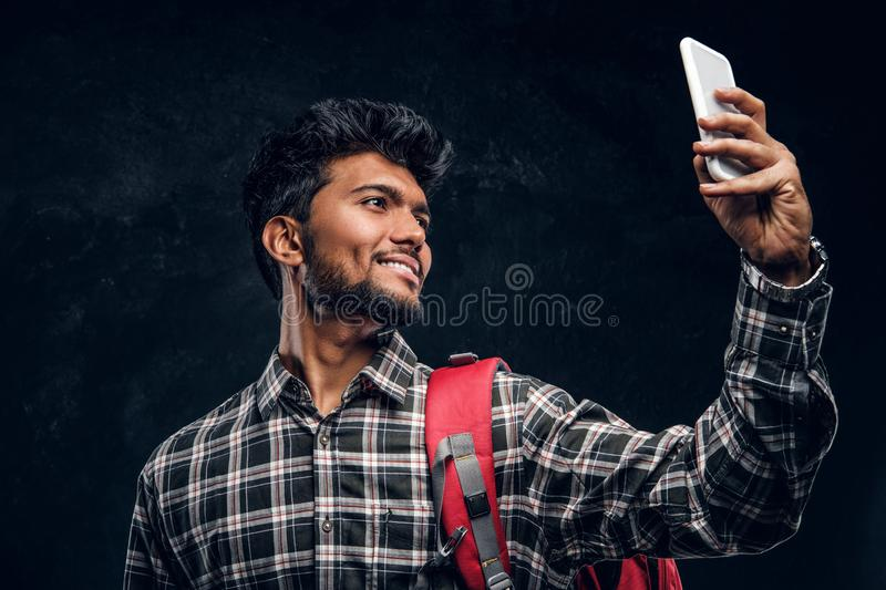 Happy Indian student with backpack taking a selfie. Studio photo against a dark textured wall stock photos