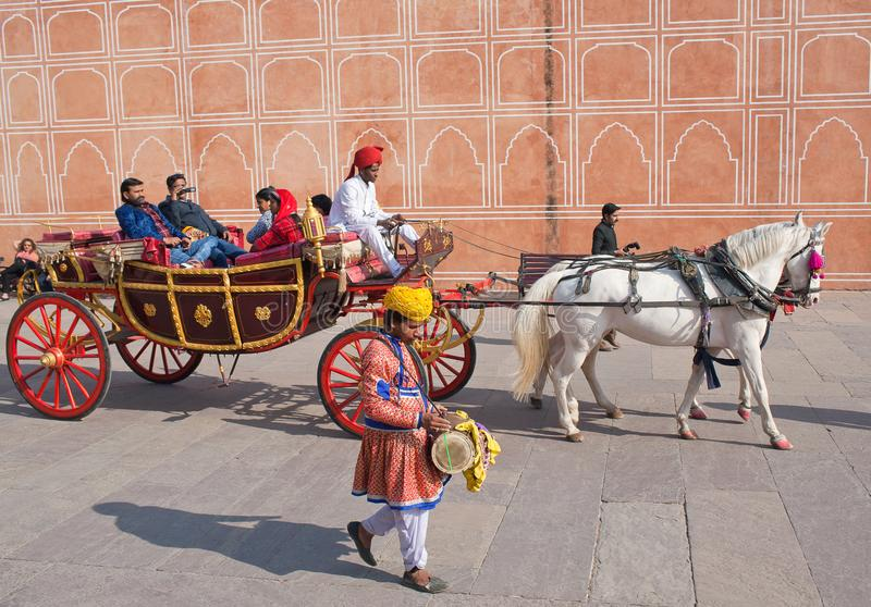 Happy Indian tourists riding a horse cart in famous Jaipur City Palace in Rajasthan, India. JAIPUR, INDIA - JANUARY 4, 2019: Happy Indian tourists riding a horse royalty free stock photos