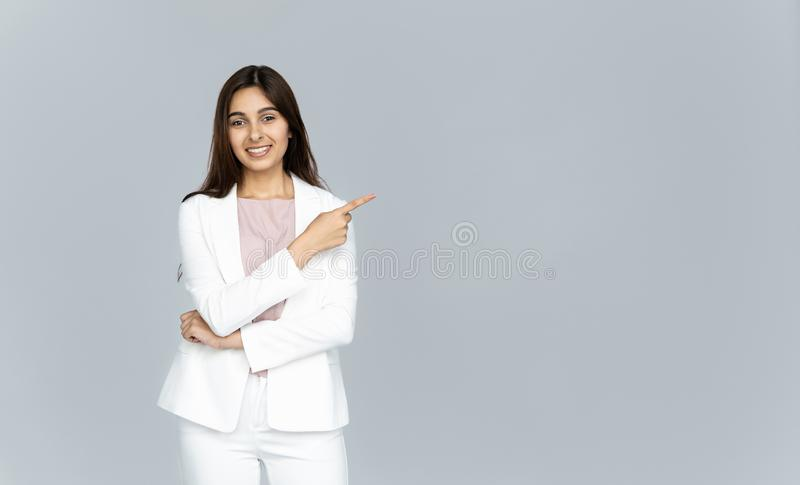 Happy indian young business woman looking at camera pointing finger at copyspace royalty free stock photos