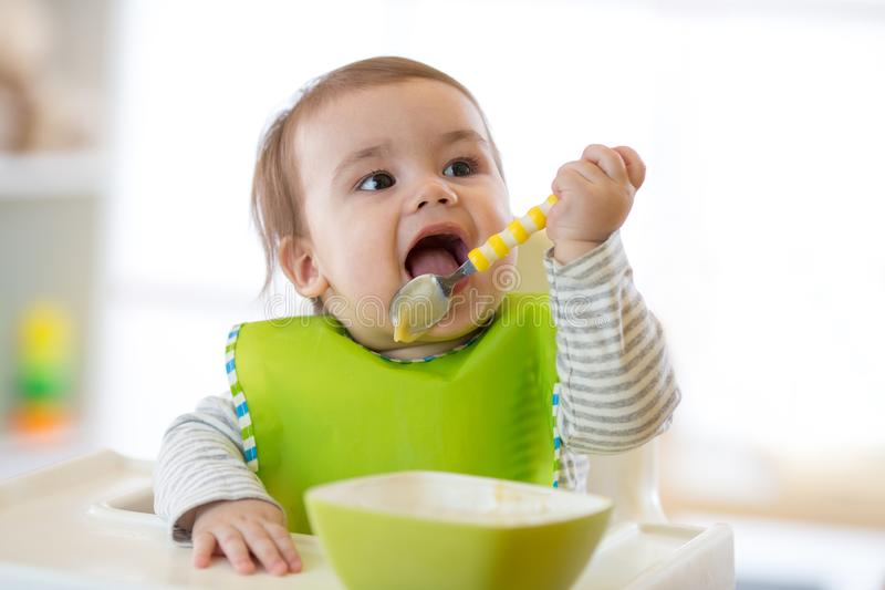 Happy infant baby boy spoon eats itself stock photos