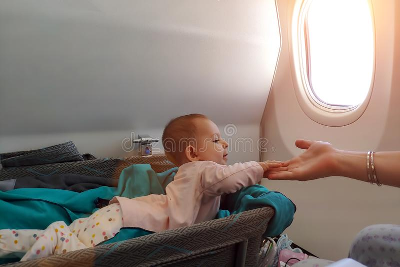 Happy infant baby lyes in special bassinet in airplane at his stomach. First flight of the baby, she is impressed and holding. Mother hand. Traveling with stock photo