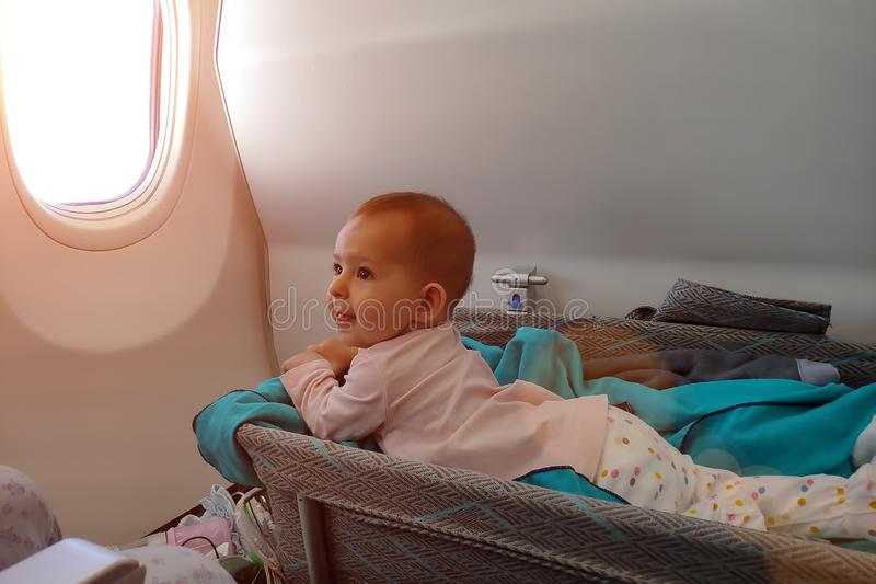 Happy infant baby lyes in special bassinet in airplane at his stomach. First flight of the baby, she is impressed and smiles. Traveling with child stock images