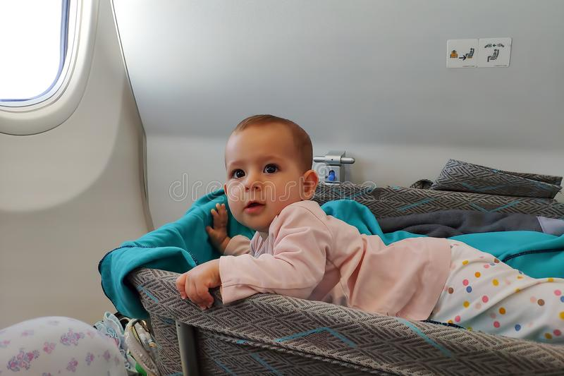 Happy infant baby lyes in special bassinet in airplane at his stomach. First flight of the baby, she is impressed. Travel with. Children stock photos