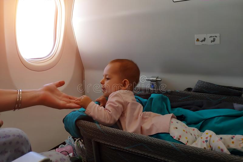 Happy infant baby lyes in special bassinet in airplane at his stomach. First flight of the baby, she is impressed and holding. Mother hand. Traveling with stock images