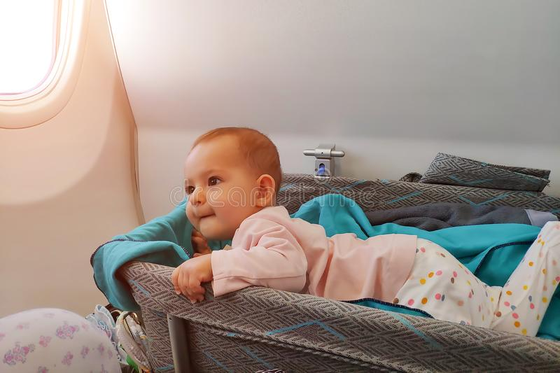 Happy infant baby lyes in special bassinet in airplane at his stomach. First flight of the baby, she is impressed and looking on. Mom stock images