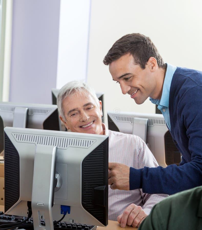 Happy Instructor Assisting Senior Man At Computer Desk stock image