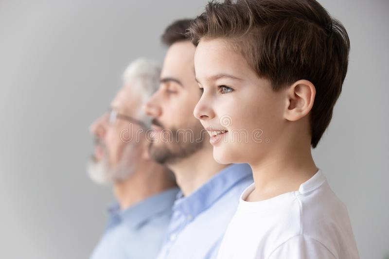 Child boy grandson stand in row with father and grandfather. Happy intergenerational muti 3 three generation men family portrait, cute child boy son grandson stock photo