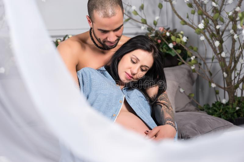 Happy international couple of man with bare chest hugging his br stock photo