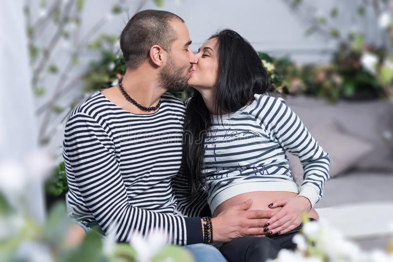 Happy international couple in striped sweaters is kissing, muslim man hugging belly of his pregnant wife while sitting on the bed royalty free stock photos