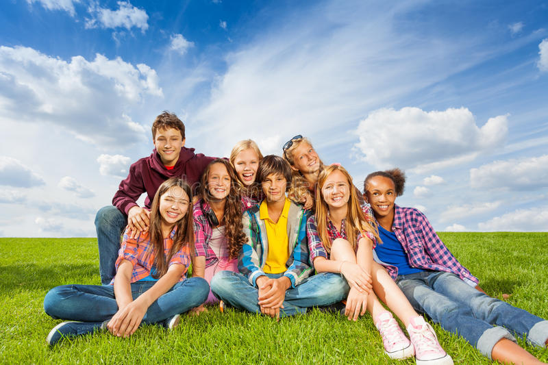 Happy international kids sit close on grass royalty free stock photography
