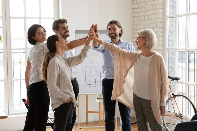 Happy international team giving high five to each other. royalty free stock photos