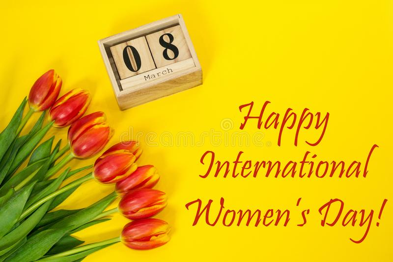 Happy International Women`s Day composition bouquet of red tulip buttons, wooden cubic calendar and greeting text. Flat lay from royalty free stock images