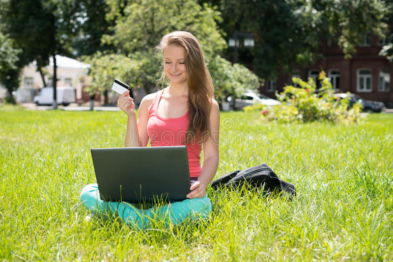Happy internet shopping woman online with laptop and credit card sitting outdoor on green grass. Internet shopper buying things on. Internet shopper buying stock image