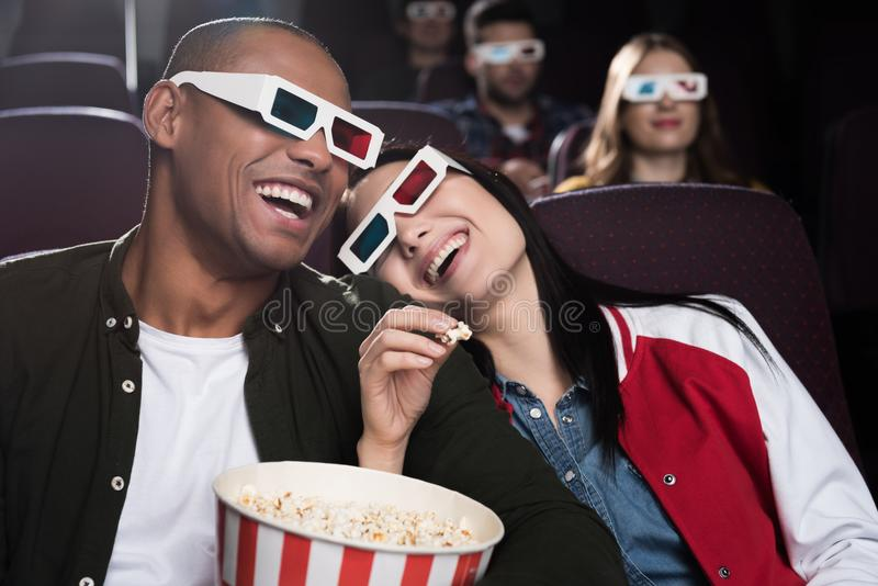 Happy interracial couple in 3d glasses eaying popcorn and watching movie. In cinema royalty free stock photography