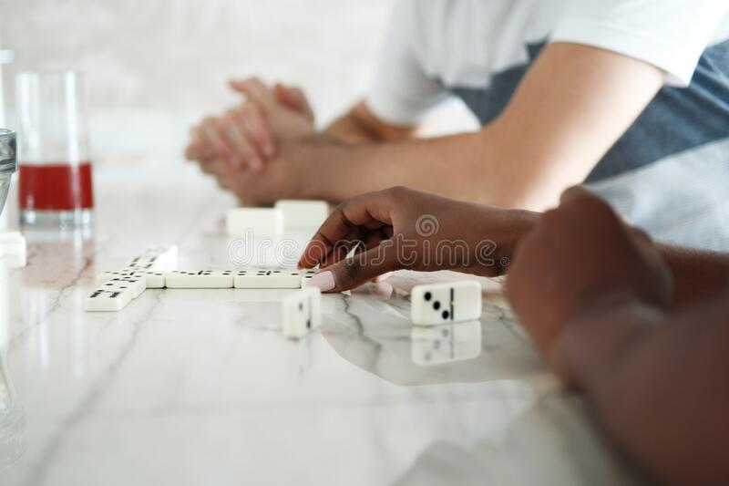 Happy Interracial Couple Having Fun Playing Domino At Home royalty free stock images