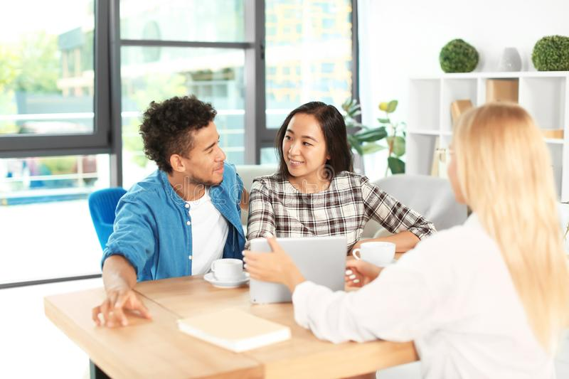 Happy interracial couple with real estate agent in office stock image