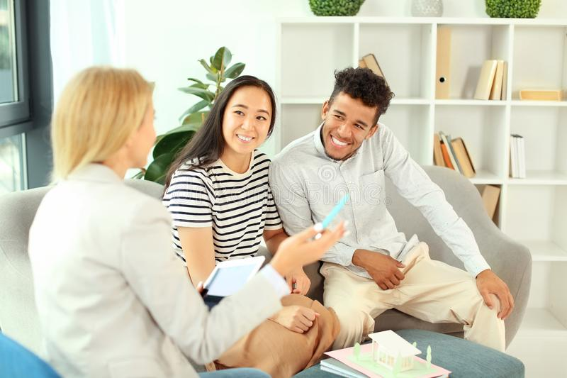 Happy interracial couple with real estate agent in office stock photos