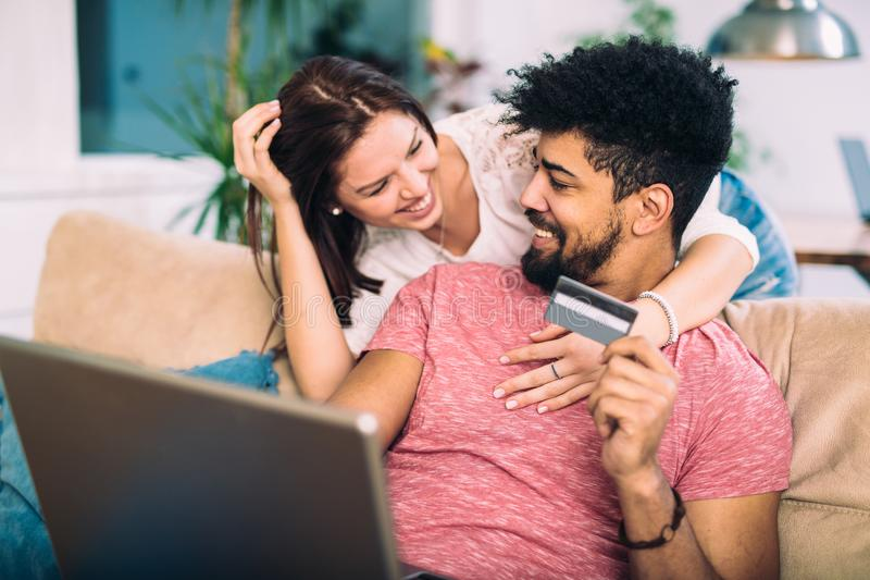 Happy interracial couple shopping online at home. Using credit card, laughing royalty free stock photos