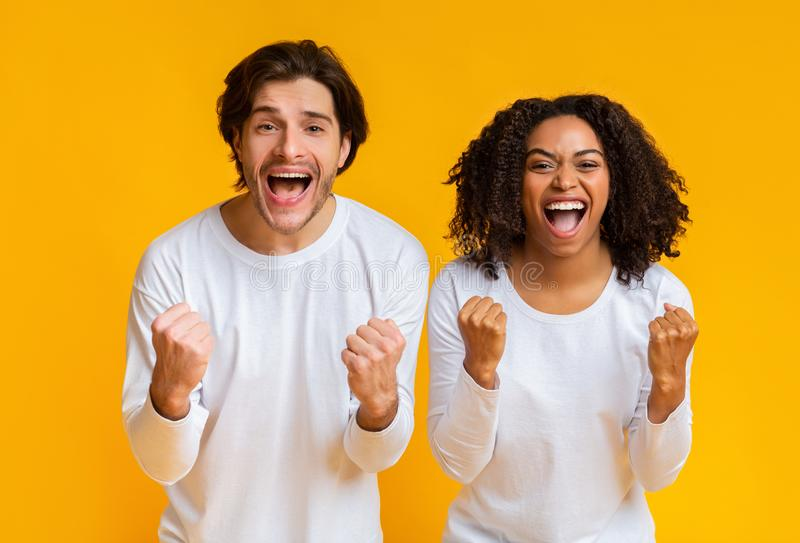 Happy interracial couple shouting and clenching fists with excitement. Yes. Happy interracial couple shouting and clenching fists with excitement, cheering and stock photography