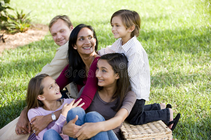 Happy interracial family of five enjoying a picnic royalty free stock image