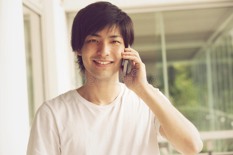 Happy japanese man on the phone royalty free stock photos