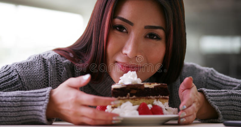 Happy Japanese woman eating cake at home royalty free stock image