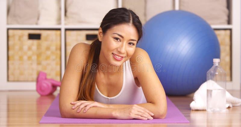 Happy Japanese woman lying on yoga matt stock photography