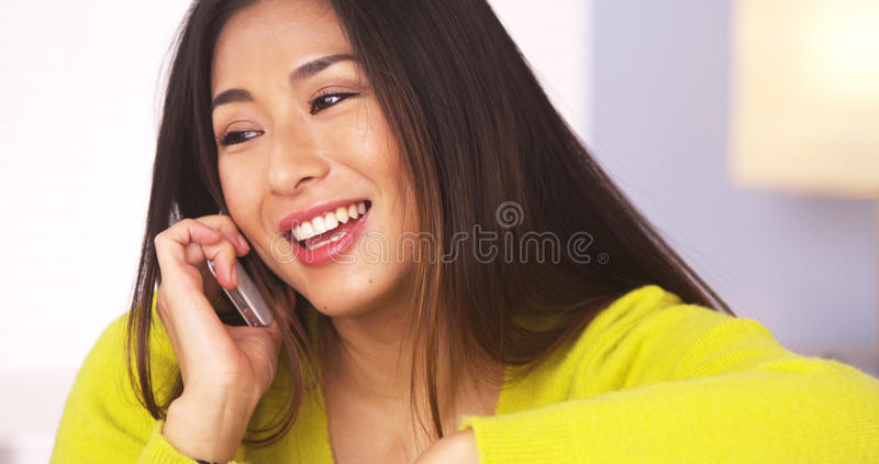 Happy Japanese woman talking on smartphone stock photo