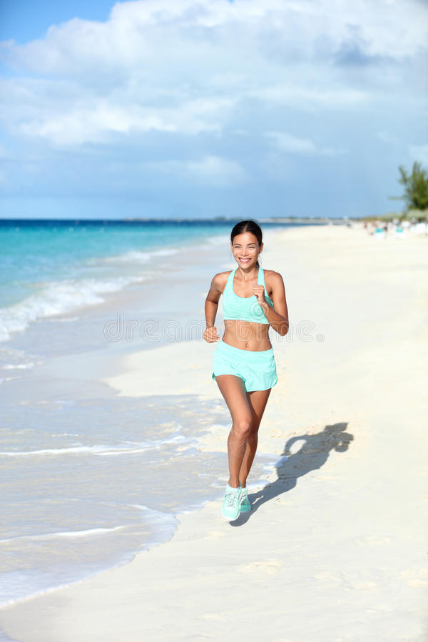 Happy jogging woman running on sunny beach living a fit life stock image