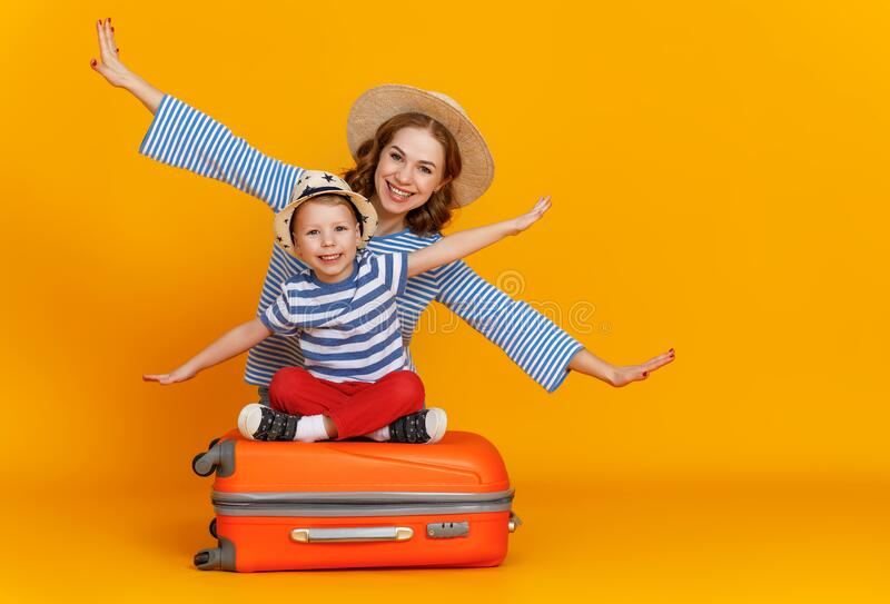 Happy journey! family of travelers mother and child  with suitcases tickets and passports on yellow background royalty free stock images