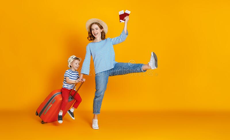 Happy journey! family of travelers mother and child  with suitcases tickets and passports on yellow background royalty free stock image