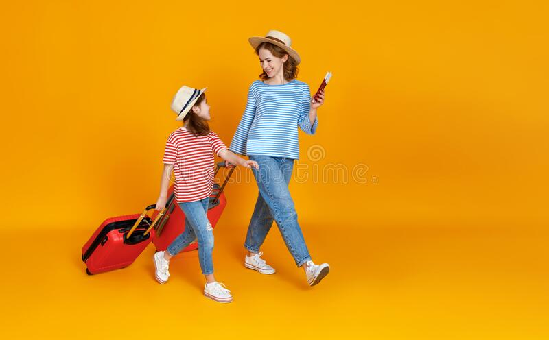 Happy journey! family of travelers mother and child  with suitcases tickets and passports on yellow background royalty free stock photography