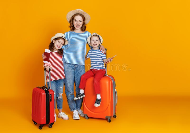 Happy journey! family of travelers mother and children with suitcases tickets and passports on yellow background royalty free stock images