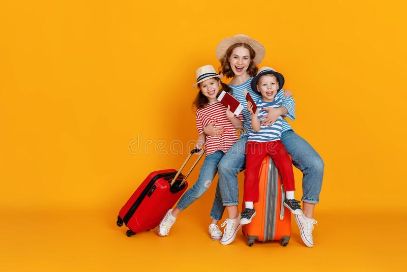 Happy journey! family of travelers mother and children with suitcases tickets and passports on yellow background stock photo