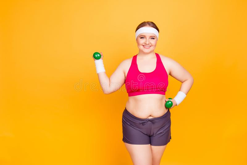 Happy joyful confident with toothy smile girl dressed in sportive outfit is lifting up green little dumbbells and training her ar stock photos