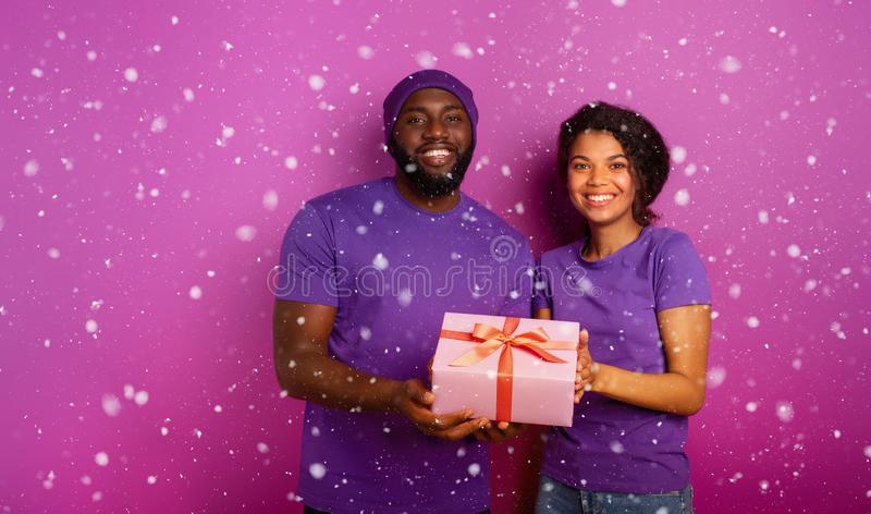 Happy and joyful couple show their Christmas present. Violet background. Happy couple show their Christmas present. Violet background royalty free stock photography