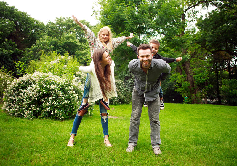 Happy joyful family in park fun playing imitation flight royalty free stock images