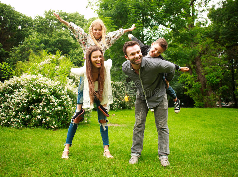 Happy joyful family in park fun playing imitation flight stock image