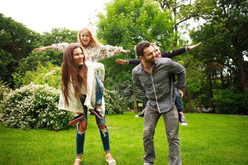 Happy joyful family in park fun playing imitation flight stock images