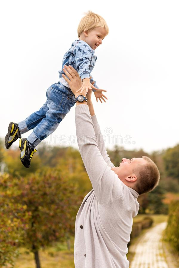 Happy joyful father having fun throws up in the air child. Family, travel, vacation, father`s day concept. stock photography