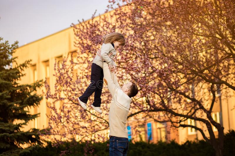 Happy father having fun throws up in air child. father`s day. single parent family stock photo