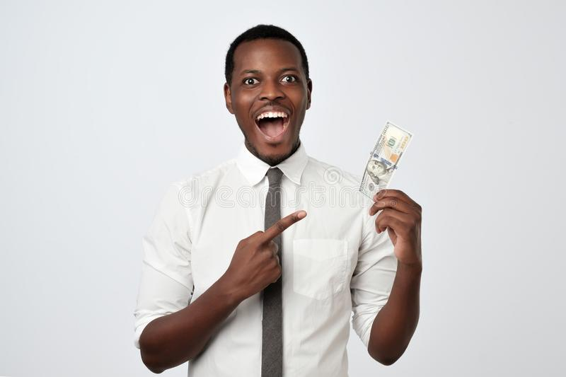 Happy joyful handsome young adult businessman holding dollars and opening mouth. royalty free stock images