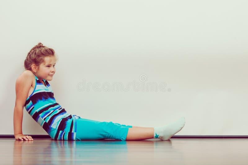 Happy joyful little girl kid sitting on floor. stock photo