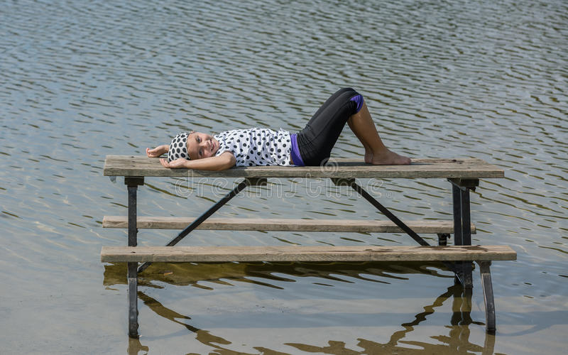 Happy joyful little girl lying and relaxing on picnic table staying in the lake. Fashionable happy joyful little girl lying and relaxing on picnic table staying royalty free stock photos