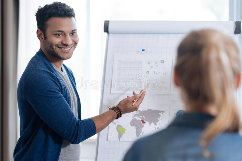 Happy joyful nice man standing in front of the flip chart stock photo
