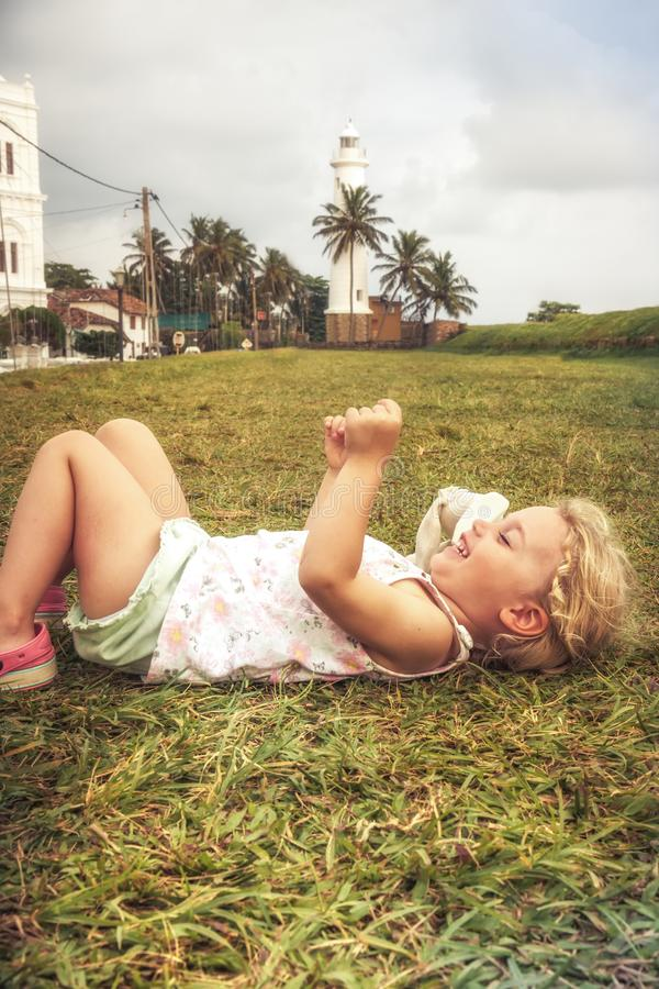 Happy joyful smiling child girl having fun lying on grass concept happiness joy childhood lifestyle stock photography
