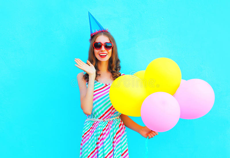 Happy joyful smiling young woman in a birthday cap with an air colorful balloons royalty free stock photos